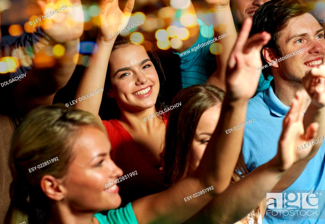 Stock Photo: party, holidays, celebration, nightlife and people concept - smiling friends waving hands at concert in club.