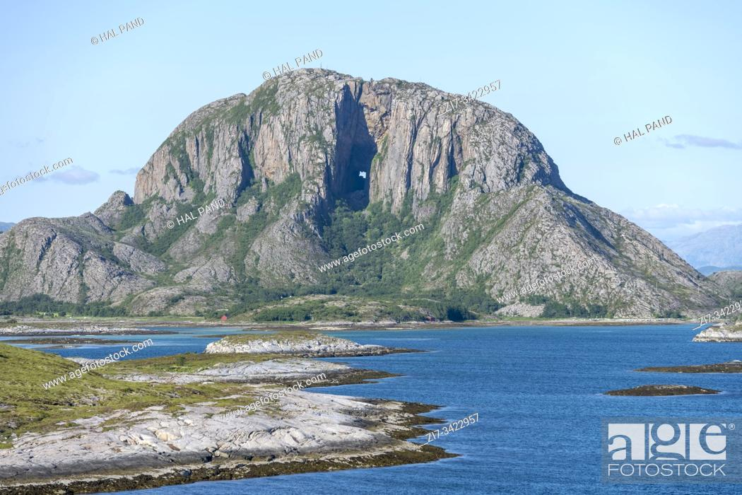 Stock Photo: fjord landscape with steep rocky hill with hole in huge cavern and cliffs archipelago, shot under bright summer light at Torget island, Norway.