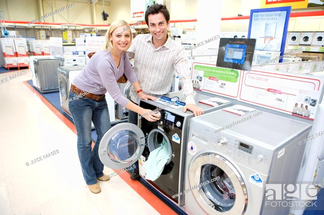 Stock Photo: Young couple shopping for washing machine, smiling, portrait.