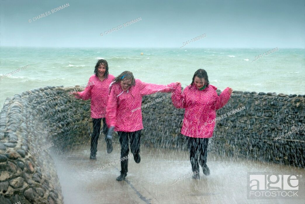 Photo de stock: teenagers pink raincoats trio.
