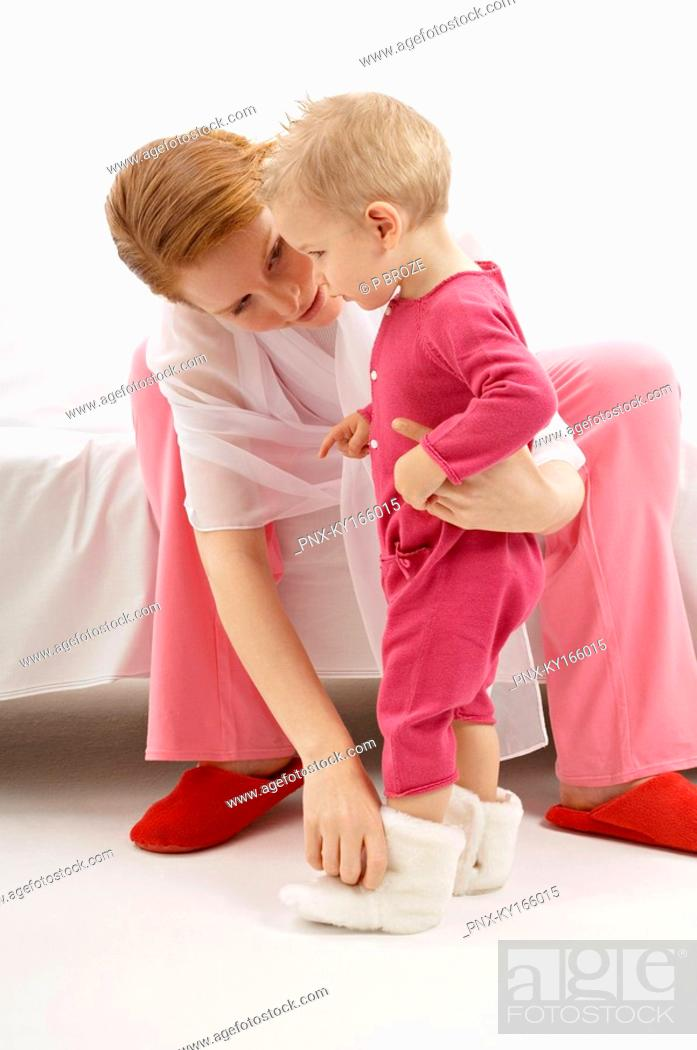 Stock Photo: Young woman putting baby booties to her son.