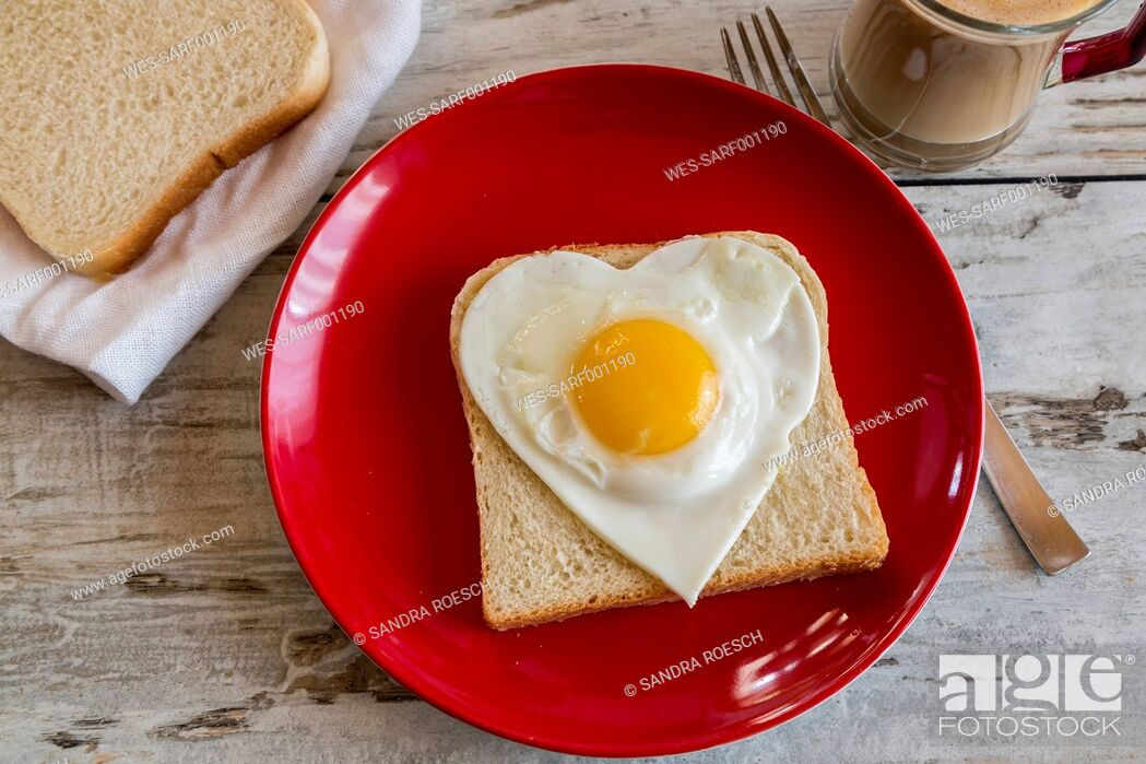 Stock Photo: Heart-shaped fried egg on toast on red plate.