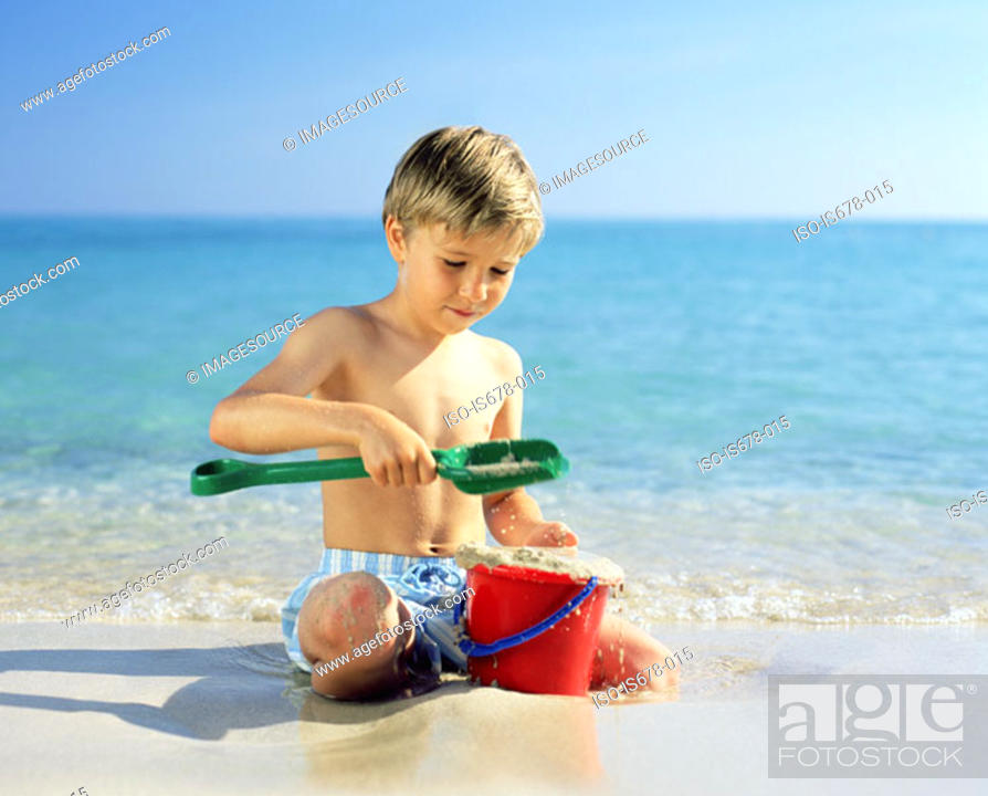 Stock Photo: Boy playing with wet sand.