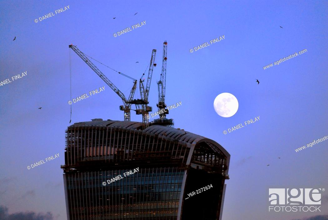Stock Photo: Building under construction in the City of London international business district at dusk under a full-moon in Winter.