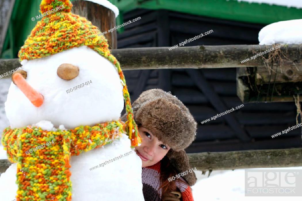 Stock Photo: Woman hiding behind snowman.