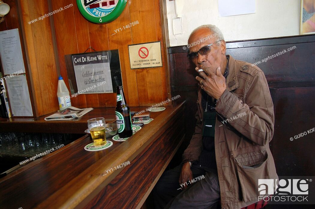 Stock Photo: Rotterdam, Netherlands. Senior adult male drinking a beer while sitting at a bar down town Nieuwe Binnenweg.
