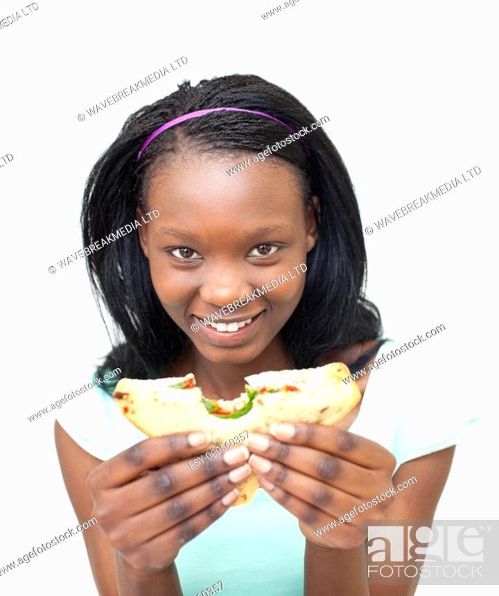 Stock Photo: Joyful young woman eating a sandwich against a white background.