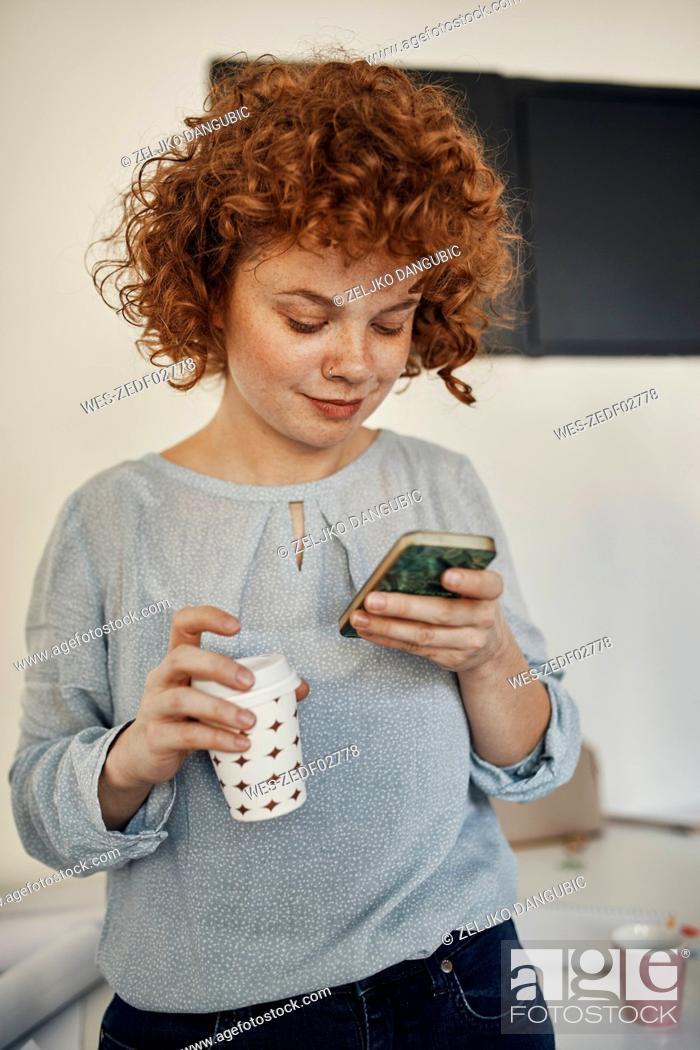 Stock Photo: Businesswoman having a break in office using smartphone.