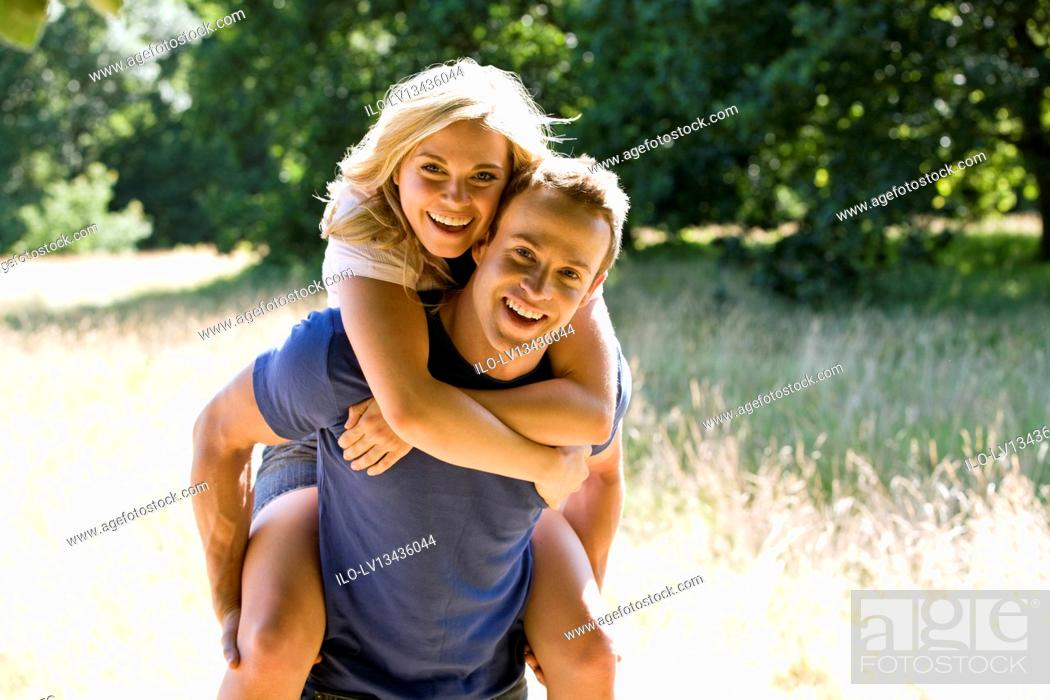 Stock Photo: A man giving his girlfriend a piggyback.