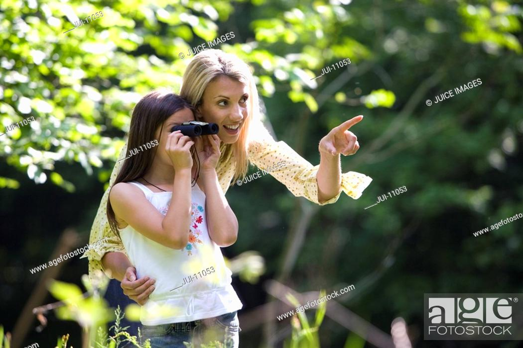 Stock Photo: Mother pointing by daughter 7-9 using binoculars in forest.