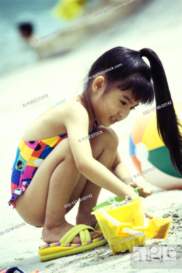 Stock Photo: Girl playing in the sand on the beach.