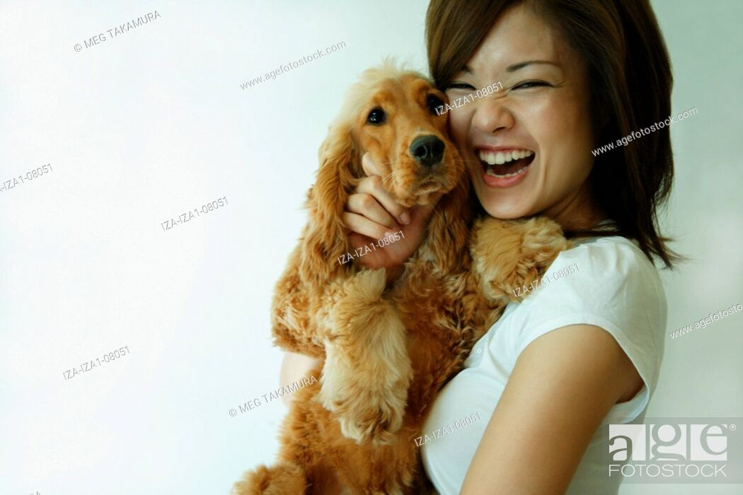 Imagen: Young woman carrying a dog and laughing.