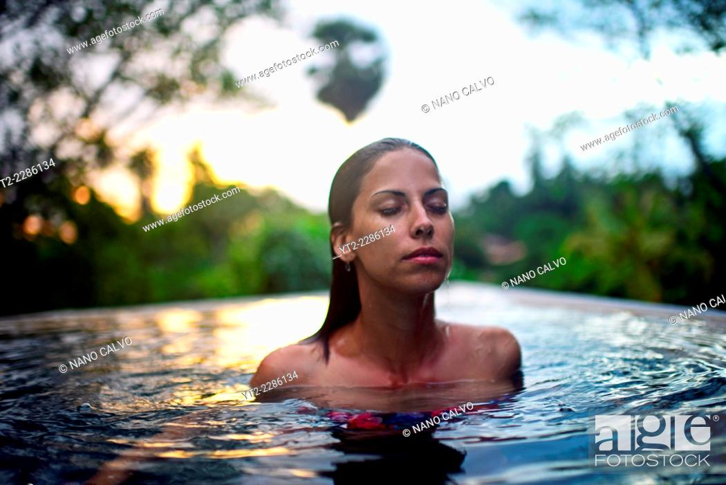 Stock Photo: Young attractive woman enjoying a bath in the infinity edge swimming pool at The Dutch House, Galle, Sri Lanka.