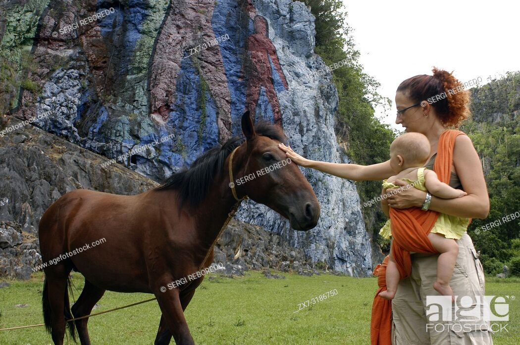 Stock Photo: Mother with her baby and a horse in The Prehistory mural, Pinar del Rio, Cuba. Painted in the wall of a cliff is one of the popular attractions in the landmark.