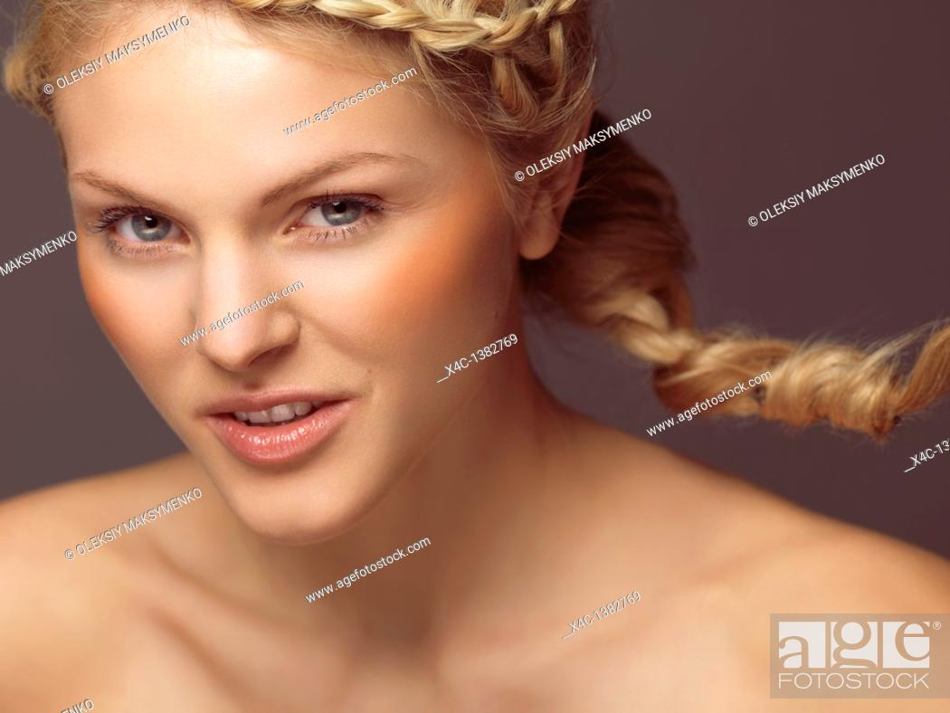 Stock Photo: Beauty portrait of a young smiling woman with a braid and orange blush.