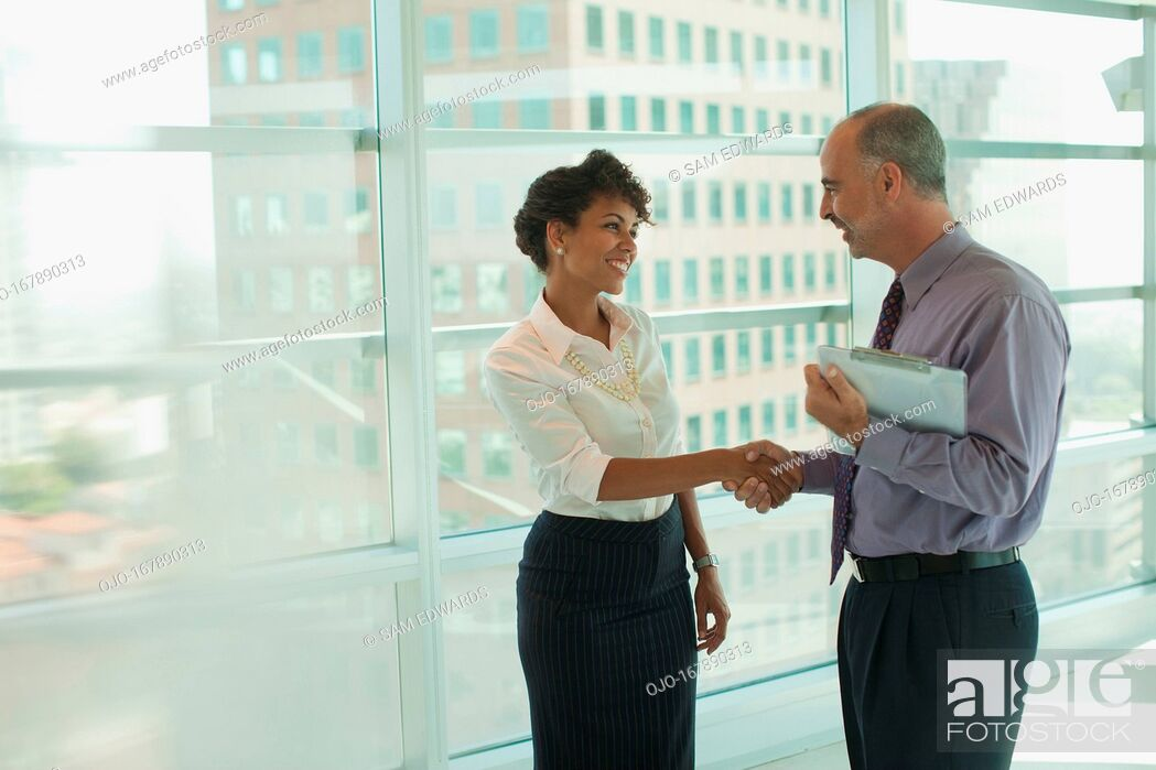 Stock Photo: Business people shaking hands in office.