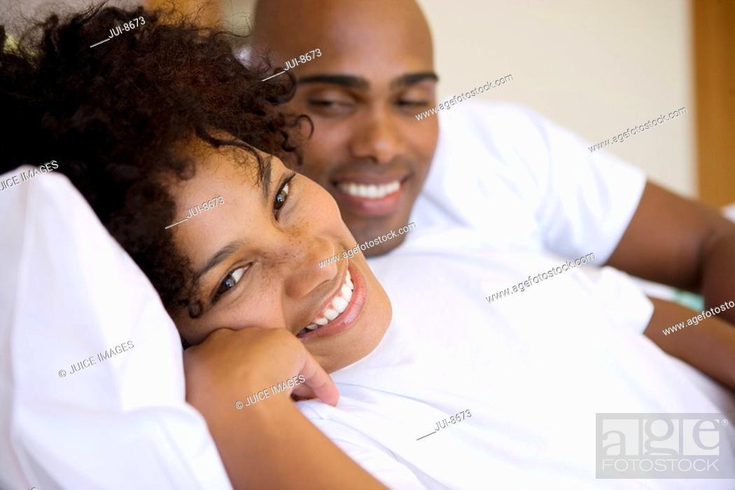Stock Photo: Young couple lying on bed smiling, portrait of woman, close-up.
