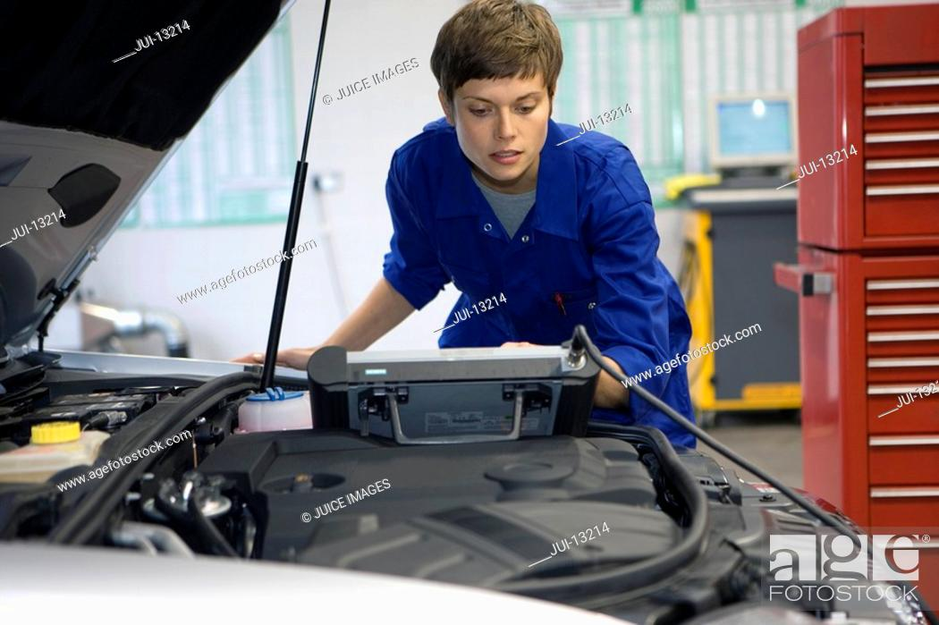Stock Photo: Female mechanic with diagnostic computer by open bonnet of car.