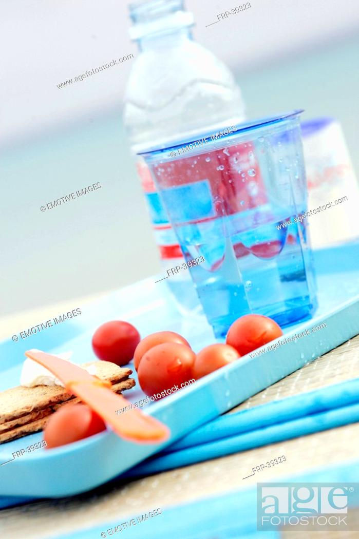 Stock Photo: A glass of water, tomatoes and crispbread on a tray.