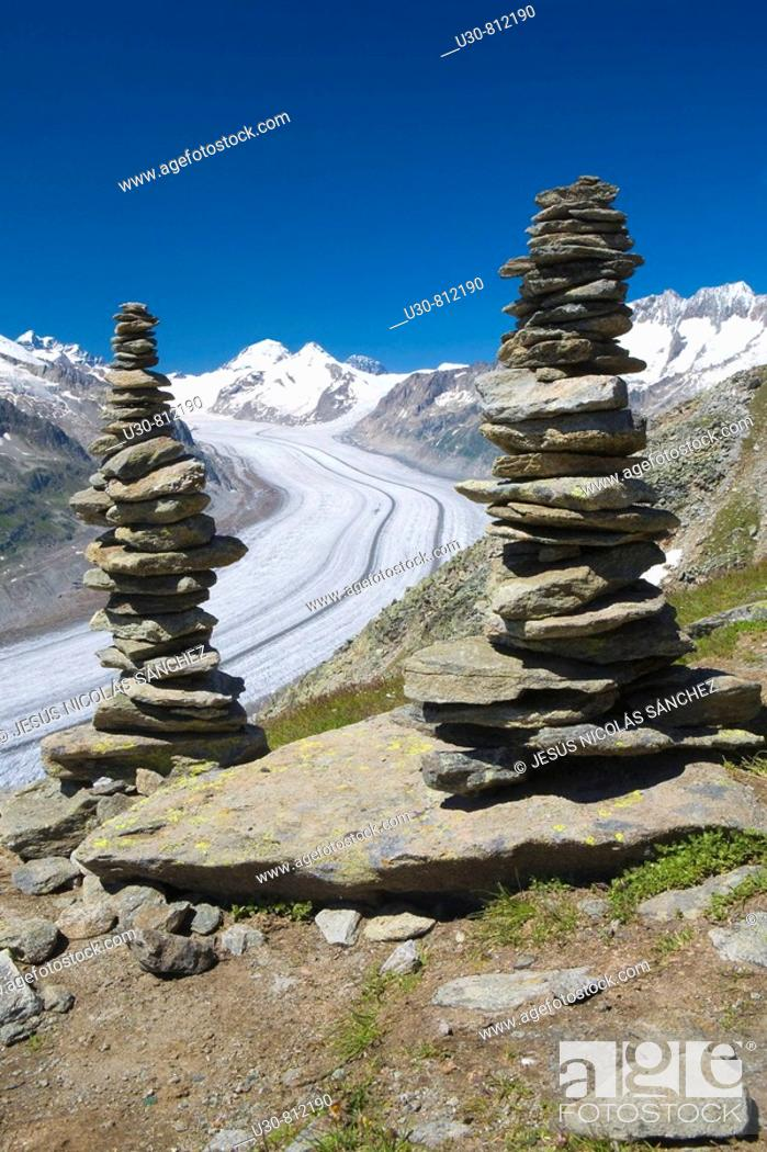 Stock Photo: Piled stones to mark the road in the mountains  Valley glacier with its longitudinal moraines of the Glacier Alesht  At the bottom the summits of the Monch.