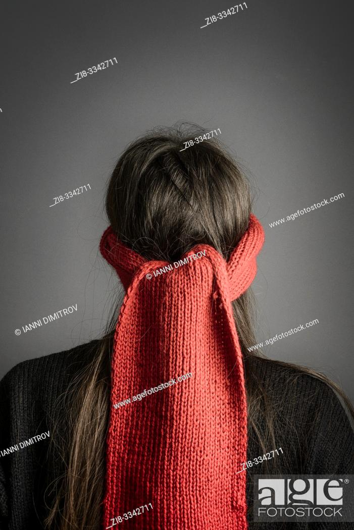 Stock Photo: Girl with dark long hair blindfolded with a red knitted scarf- back view.