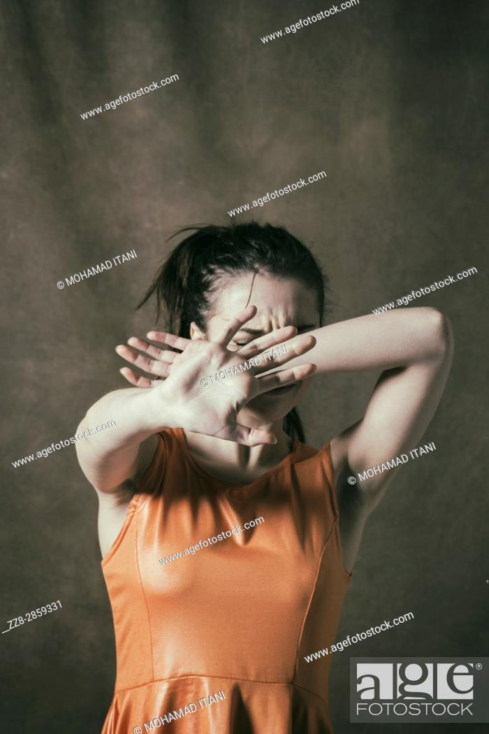 Stock Photo: Scared young woman hiding face with hands.