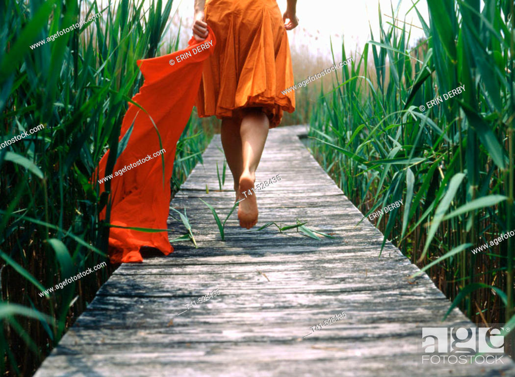 Stock Photo: A woman takes a stroll down a pier in Mattituck, NY. She carries the red sarong. USA.