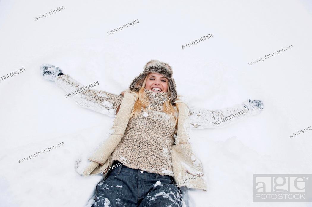 Stock Photo: Austria, Salzburg County, Mid adult woman lying on snow, smiling.