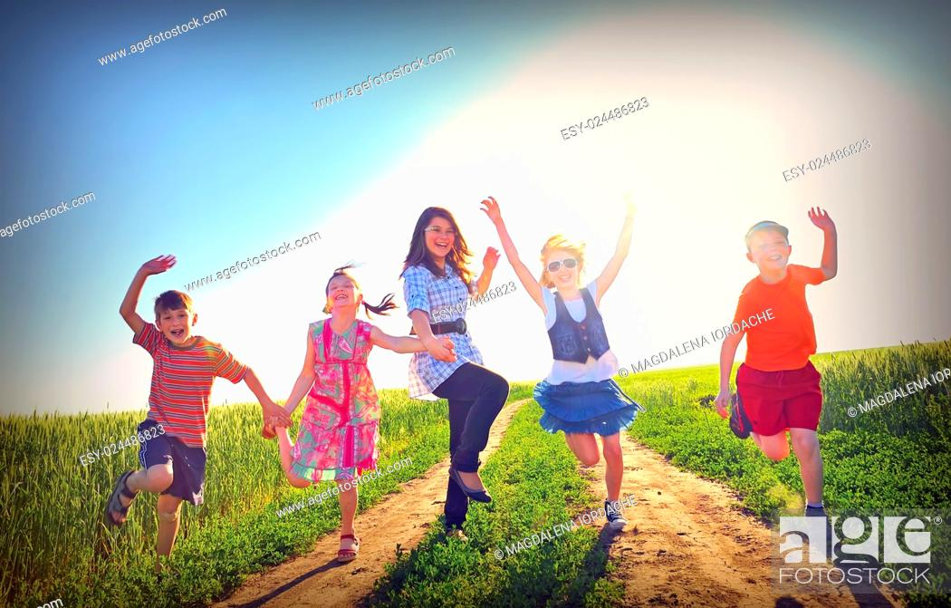 Imagen: happy children play on field in summer time.