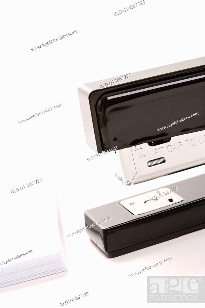 Stock Photo: Close up of black stapler on white background with stack of paper.