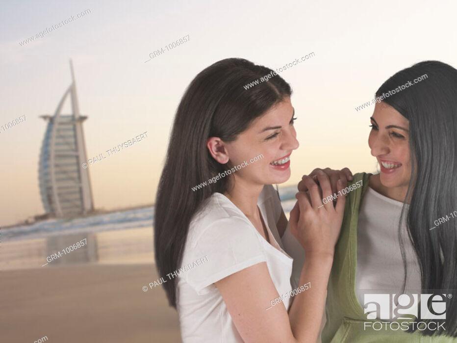 Stock Photo: Two women on the beach in Dubai with Burj Al Arab Hotel in background.