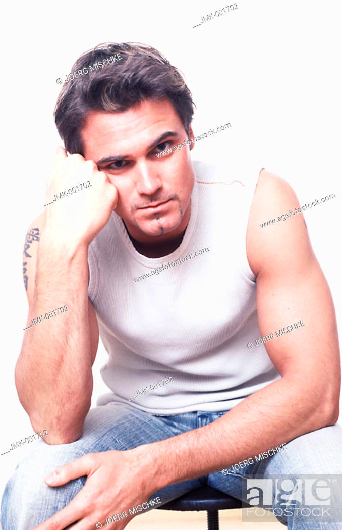 Stock Photo: Portrait of a young man, 20-25 25-30 30-35 dark-haired, masculine, powerful, strong, athletic and beautiful in a white sleeveless tee-shirt and jeans.