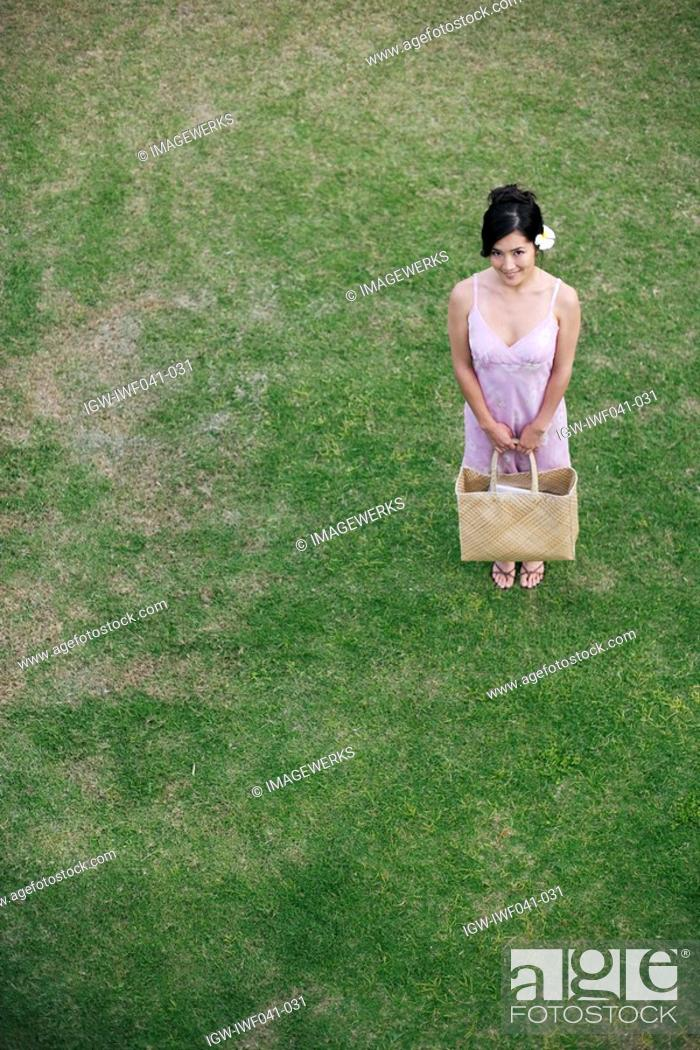 Stock Photo: A young woman standing in field.