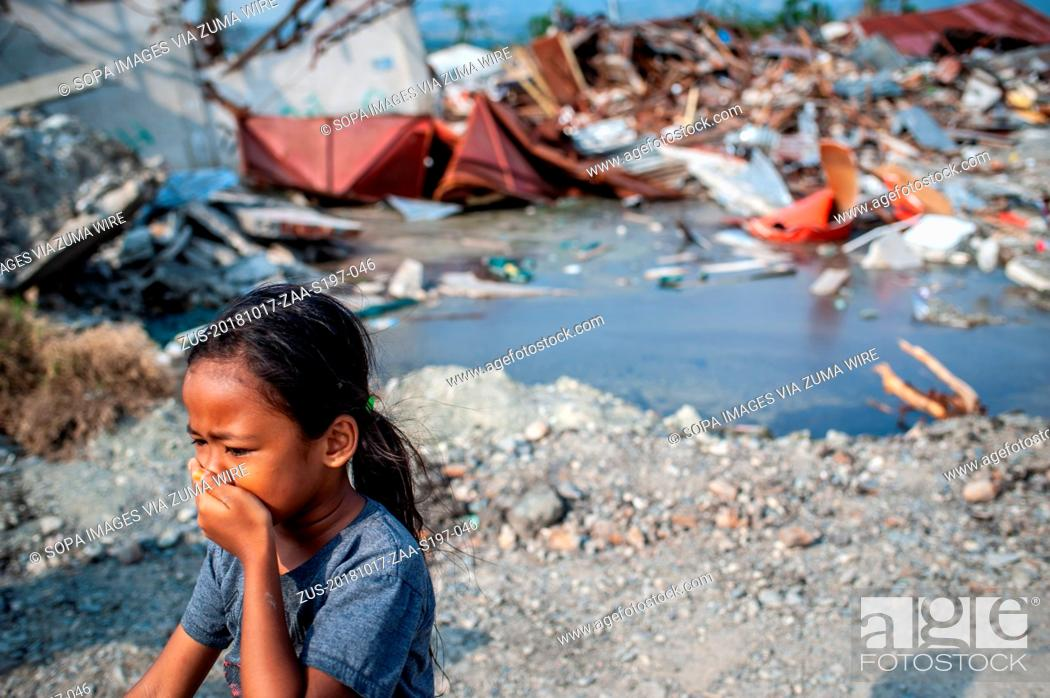 Stock Photo: October 17, 2018 - Sigi, Center Sulawesi, Indonesia - A resident is seen walking next to the ruins of a building that was destroyed by the earthquake.