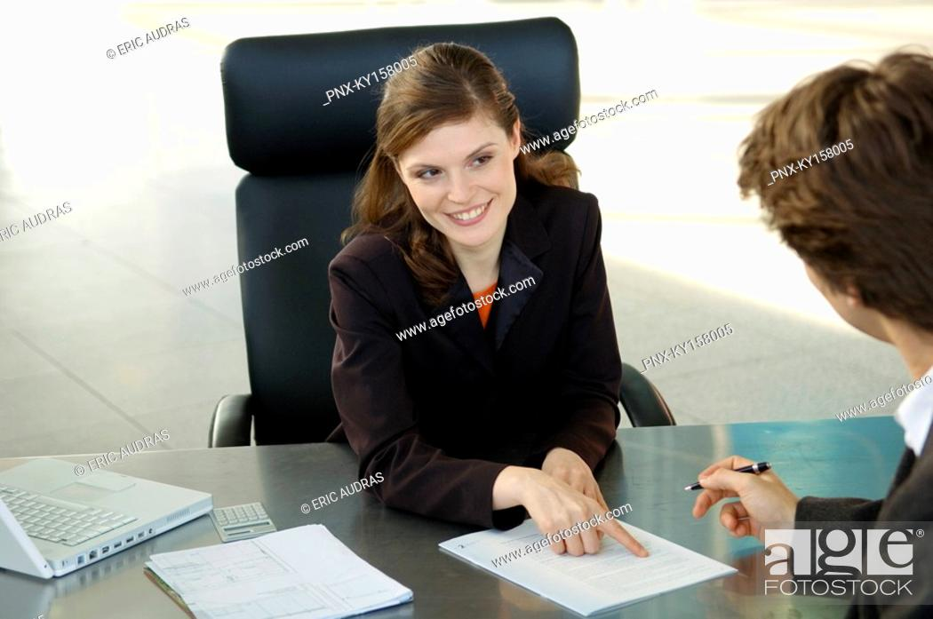 Stock Photo: Businesswoman pointing at a contract and businessman sitting in front of her.