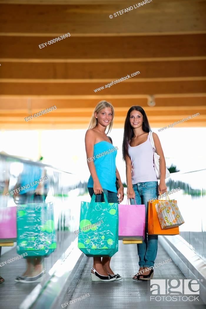 Stock Photo: Beautiful teenage girls on escalator at shopping center.
