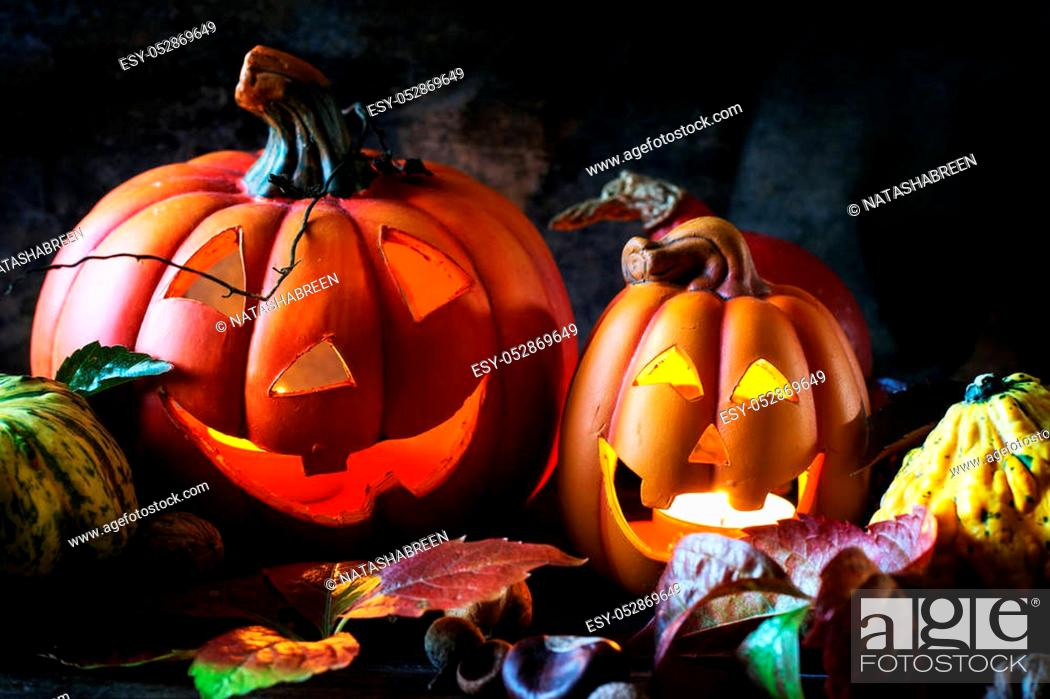 Stock Photo: Halloween's pumpkins with autumn leaves on wooden table. See series.
