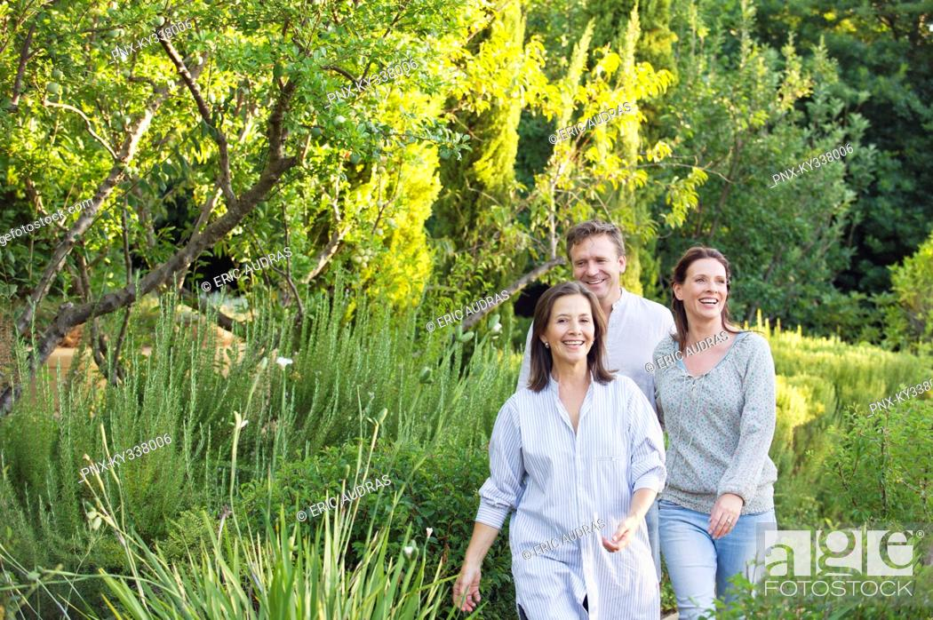 Stock Photo: Mature couple walking with their mother in a garden.