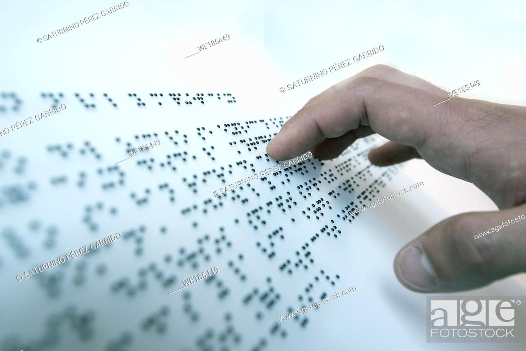 Stock Photo: Hand of a blind person reading a text in the language of the blind, Braille.