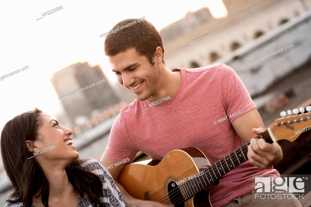 Imagen: A man playing a guitar to a woman, on a rooftop terrace overlooking a city at dusk.