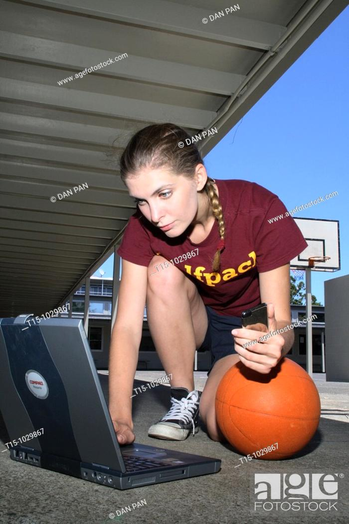 Stock Photo: woman using a laptop in a basketball court.
