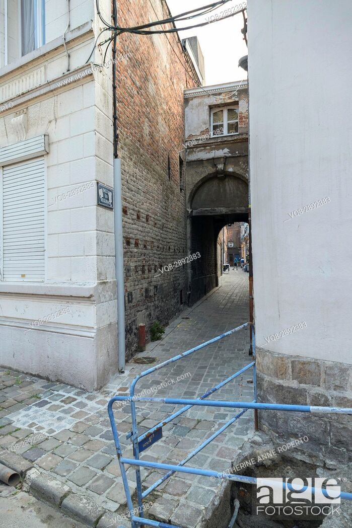 Stock Photo: Hidden alley with broken pavement leading to historic coutyard of the Beguines community of religious women, Valenciennes, France.