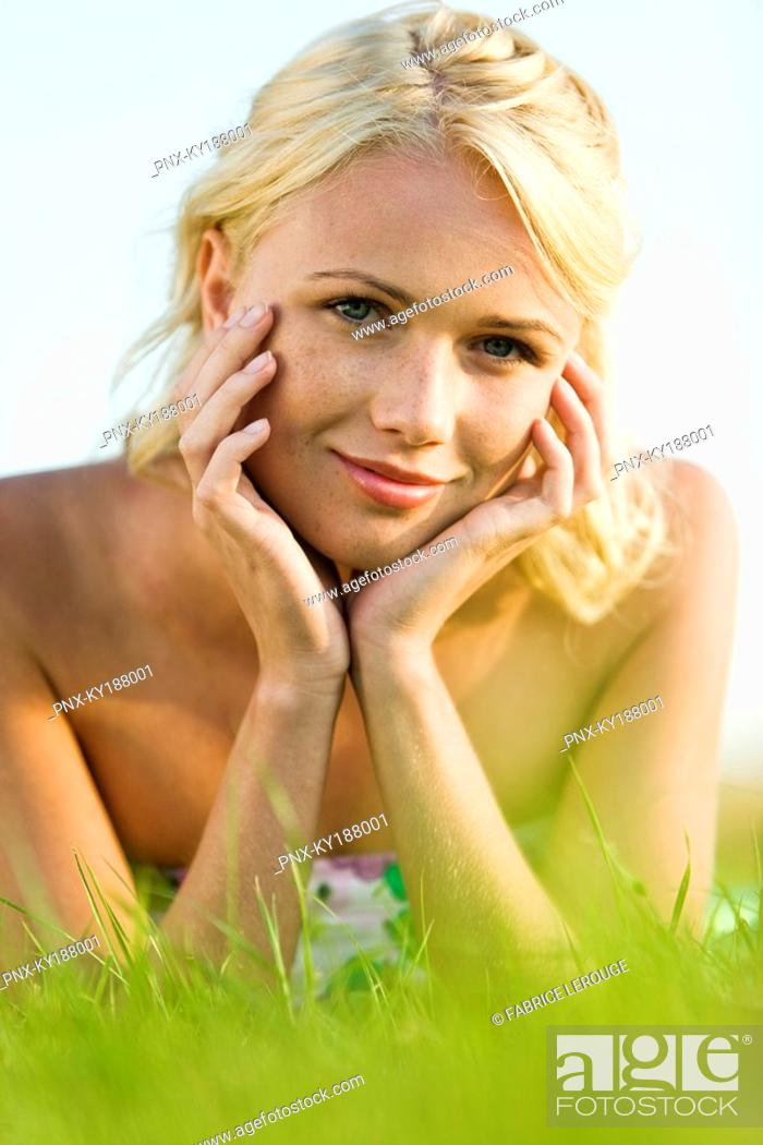 Stock Photo: Young woman lying in grass.