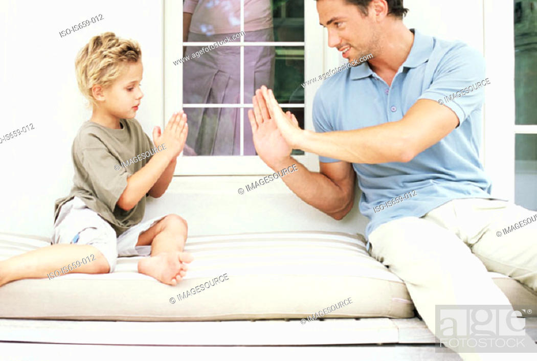 Stock Photo: Father and son playing hand clapping game.