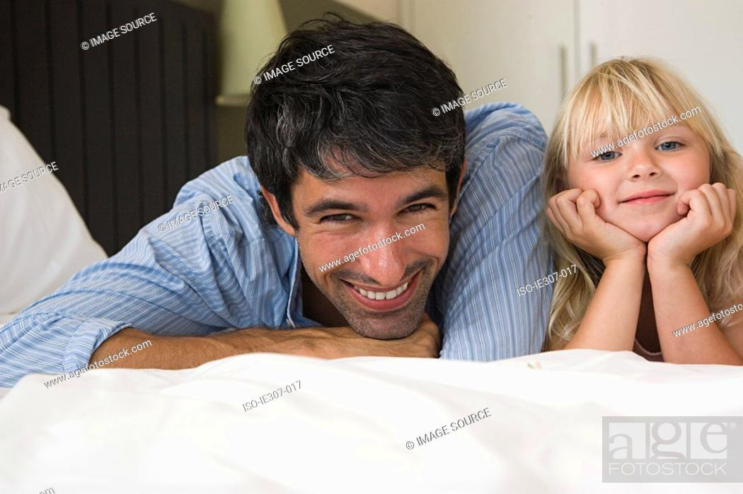 Stock Photo: Father and daughter lying on a bed.