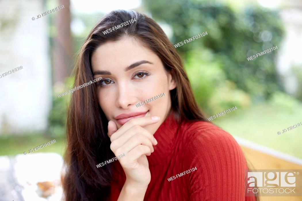 Stock Photo: Portrait of smiling woman with hand on chin.