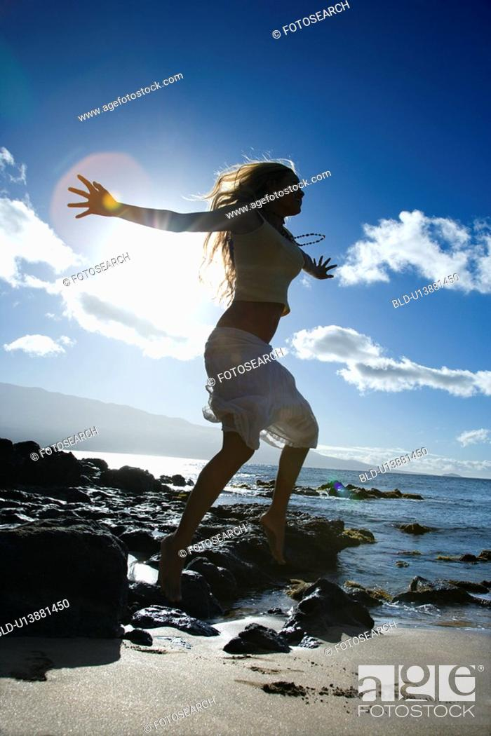 Stock Photo: Young adult Asian Filipino female jumping on beach.