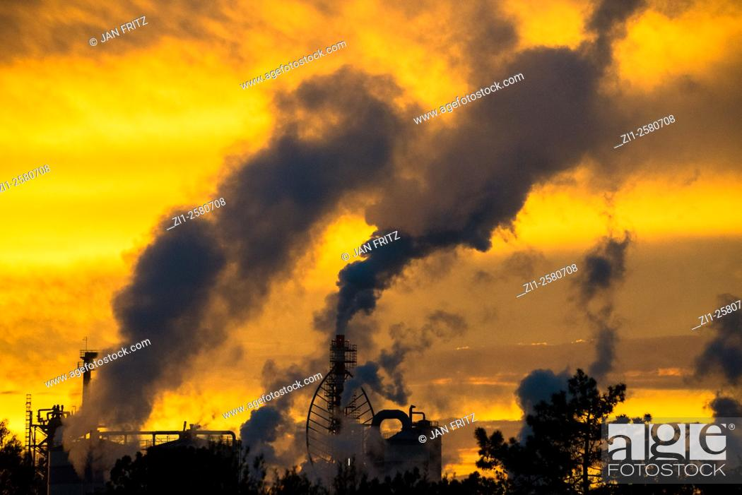 Photo de stock: black smoke from plant against orange yellow sky of sunset.