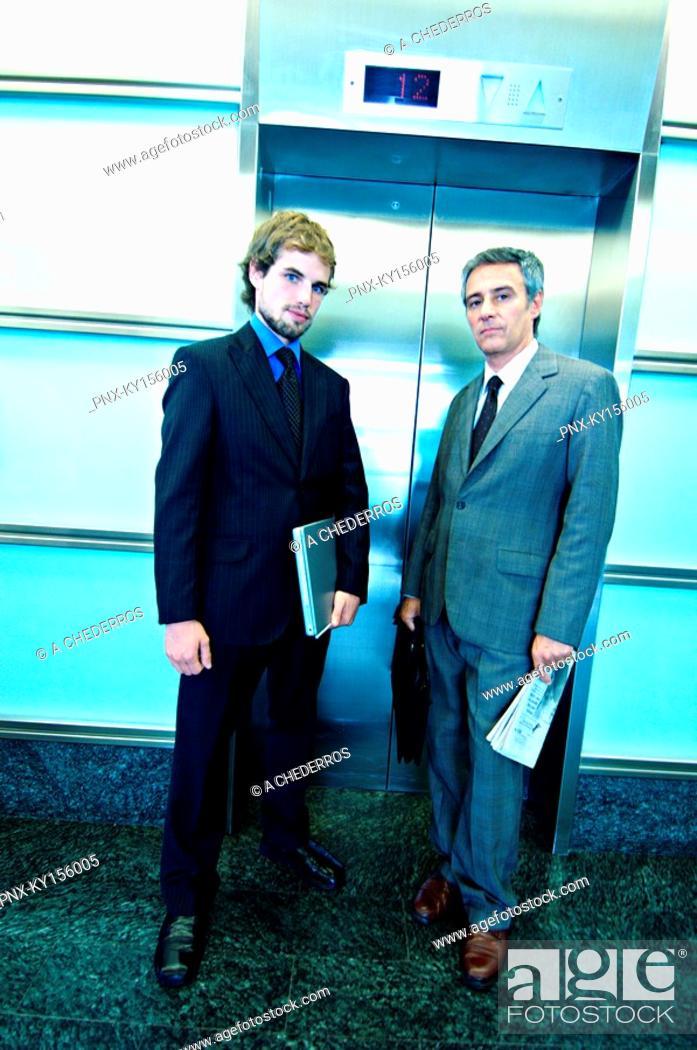 Stock Photo: Businessmen waiting for elevator, portrait.