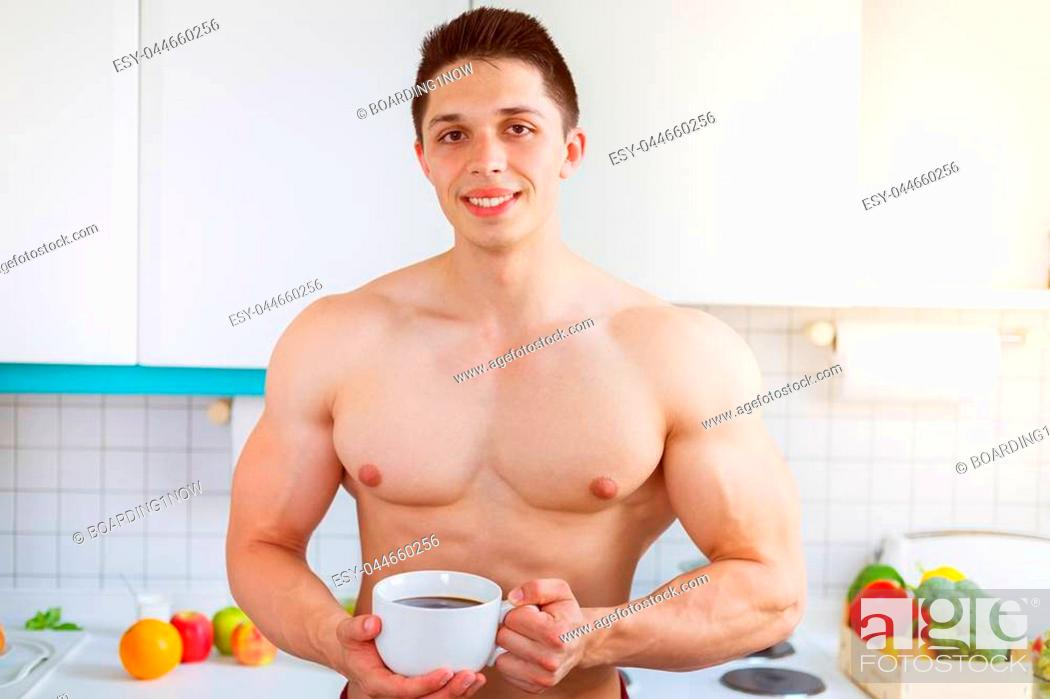Stock Photo: Bodybuilder young man shirtless drinking coffee in the kitchen morning smiling.